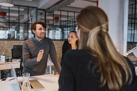 stock photo of coworkers  - Young man explaining new business plan to coworkers during a meeting around a table in office - JPG