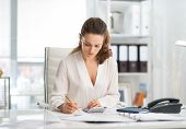 stock photo of crunch  - An elegant businesswoman is concentrating while sitting at her desk in a modern office crunching numbers - JPG