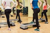 picture of step aerobics  - Group of young sportive women making step aerobics in the fitness class  - JPG