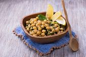 foto of chickpea  - Spiced chickpeas with spinach in a wooden bowl - JPG