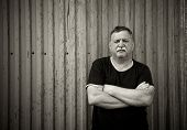 foto of 55-60 years old  - Mature mustachioed man sitting against the wall - JPG