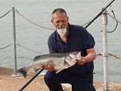 foto of specimens  - A fisherman with his rod caught specimen seabass of 9lb 11oz - JPG