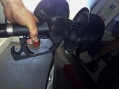 stock photo of petrol  - A mans hand filling petrol on a black car - JPG