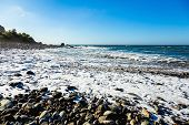 stock photo of atlantic ocean  - Wild stone beach on coast or shore of the Atlantic ocean with waves and foam and blue sky and horizon in Tenerife Canary island Spain at spring or summer - JPG