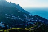 stock photo of atlantic ocean  - City or village and winding or serpantine road in green mountain or rock valley and clouds with horizon landscape near shore of Atlantic ocean in Tenerife Canary island Spain - JPG