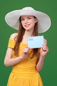 stock photo of post-teen  - Smiling bright woman in summer dress and white hat showing blank envelope banner - JPG