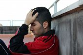 stock photo of sob  - downcast young guy looking down with hand on forehead - JPG