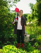 stock photo of spade  - Happy smiling girl posing at garden with spade and watering can - JPG