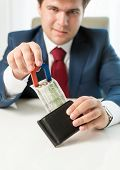 picture of greedy  - Portrait of greedy businessman pulling money out wallet with use of magnet - JPG