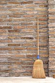 foto of broom  - Household Used Broom For Floor Dust Cleaning Leaning on Brick Wall - JPG