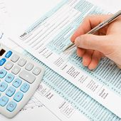 stock photo of cpa  - Male filling out US 1040 Tax Form  - JPG