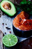 foto of over counter  - Uncooked salmon steak avocado lime and parsley over old wooden texture  - JPG