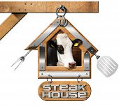 picture of food chain  - Wooden and metallic sign in the shape of house with text Steak House head of cow spatula and fork - JPG