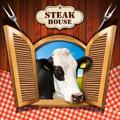 image of cow head  - Wooden wall with checkered tablecloth and an open window with a head of cow label with text Steak house and two steel forks - JPG