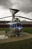 pic of helicopters  - Blue helicopter standing on the lawn under the cloudy sky - JPG