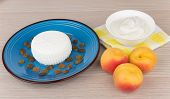 foto of curd  - Granular curd and raisins in blue plate sour cream and peaches on table - JPG