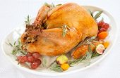 foto of kumquat  - Roasted turkey on tray garnished with red grapes figs kumquat and herbs over white background - JPG