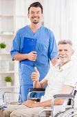 foto of male nurses  - Kind male nurse and his senior patient in wheelchair at hospital - JPG