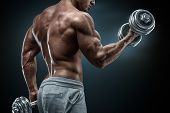 picture of shoulder muscle  - Handsome power athletic man in training pumping up muscles with dumbbells - JPG