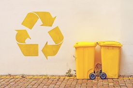 foto of recycle bin  - Two Yellow Plastic Recycle Bins on the Street Against White Wall with Recycle Symbol Stencil Graffiti Toned Image - JPG