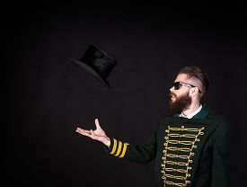 image of queer  - Magician throwing hat up in the air - JPG