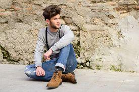 image of suspenders  - Portrait of young man wearing suspenders sitting on the floor in urban background - JPG
