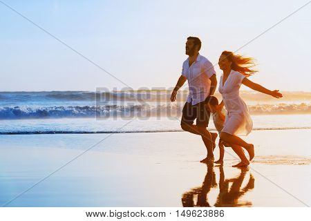 Happy family - father mother baby son hold hands and run together with fun along sunset sea surf on black sand beach. Travel active lifestyle parents with children on tropical summer vacations.