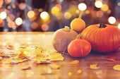 food, halloween, harvest, season and autumn concept - close up of pumpkins and leaves on wooden tabl poster