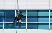 stock photo of cleaning service  - A man cleaning windows on a high - JPG