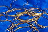 Thin Gold Bangles Scattered On A Blue Textile