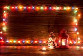 Постер, плакат: Christmas Lights And Vintage Lantern On Wooden Background