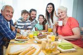 Portrait of happy multi-generation family sitting at breakfast table in home poster