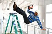 Hispanic worker falling from ladder inside building poster