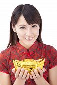 Beautiful asian woman wear cheongsam and holding chinese gold ingot
