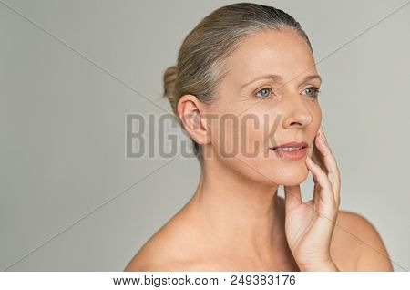 poster of Portrait of mature woman with bare shoulder isolated on gray background. Beautiful middle aged femal