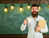 Teacher In Eyeglasses Holds Book And Mug Of Coffee Or Tea. Man With Beard On Happy Face In Classroom poster