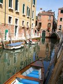 Boats and their reflections in a canal in Venice, Italy
