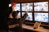 Security guards working in surveillance room poster