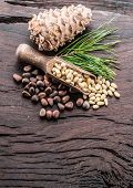 Pine nuts in the scoop and pine nut cone on the wooden table. Organic food. poster