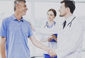 Patient And His Confident Doctor Shake Hands. Successful Treatment Of Happy Patients. Healthcare Con poster