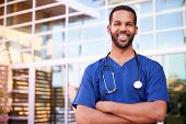 Young black male healthcare worker smiling outside, portrait poster