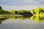 Постер, плакат: The Belarusian Landscape The Pripyat River The Shore In The Rays Of The Evening Sun And Thunderclo