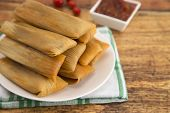 Plate Filled With Homemade Tamales Ready For Dinner On A Wooden Table poster