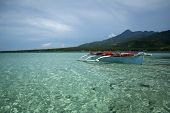 image of camiguin  - traditional banka outrigger boat in clear waters of camiguin island in the philippines - JPG