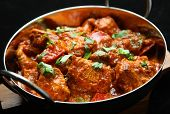 Indian chicken jalfrezi curry. Shallow DoF, focus on central chicken piece.