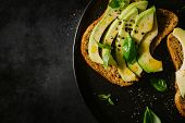 Fresh Ready Served Avocado Toasts With Spices On Dark Table. Ready To Eat. Closeup poster