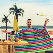 Handsome Positive Mexican Bartender In Colorful Poncho Throws Up A Bottle Of Alcohol Near The Bar Co poster