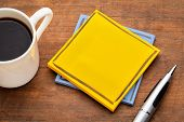 yellow, blank reminder note on a grunge wooden table with a cup of espresso coffee poster