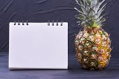 Ripe Pineapple And Blank Paper Notebook. Healthy Fresh Ananas And Paper Notepad On Black Background  poster