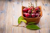 Fresh Cherry In Ceramic Ware On A Wooden Background. Fresh Ripe Cherry. Cherries. poster